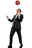 One business man playing juggling soccer ball. One caucasian business man playing juggling soccer ball in studio isolated on white background Royalty Free Stock Image