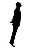 One business man silhouette tiptoe looking up. One caucasian business man silhouette standing tiptoe looking up Full length in studio isolated on white Royalty Free Stock Photos