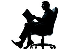 One business man sitting in armchair reading Stock Images