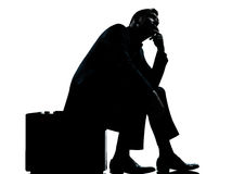 One business man sitting on suitcase waiting silhouette Stock Images