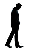 One business man walking looking down silhouette. One caucasian business man walking silhouette Full length in studio isolated on white background royalty free stock photography