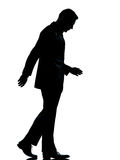 One business man walking looking down silhouette. One caucasian business man walking silhouette Full length in studio isolated on white background stock photo