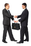 One businessman gives another briefcase full body Royalty Free Stock Image