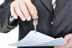 One businessman hand and the key Royalty Free Stock Photos