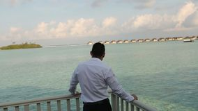 One businessman in official suit standing on the balcony of his villa bungalow and looking to the beautifull blue lagoon stock footage