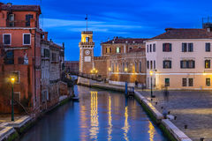 One of the canals in Venice and the Arsenal Tower in the distanc Royalty Free Stock Photos