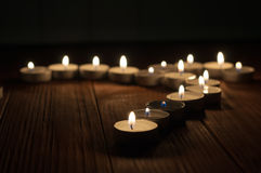 One candle and Candles on old wooden background Royalty Free Stock Image