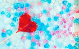 One candy heart shape against the background of transparent, white, pink and blue ice cubes. Fresh summer pattern with copy space stock photos
