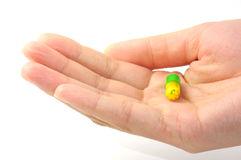 One capsule with yellow and green color in a beautiful woman hand Stock Photos