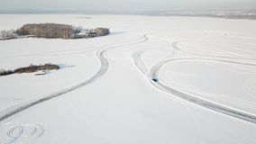 One car driving through the winter forest on country road. Top view from drone. Aerial view of snow covered road in Royalty Free Stock Images