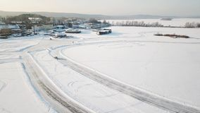 One car driving through the winter forest on country road. Top view from drone. Aerial view of snow covered road in Stock Photos