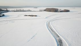 One car driving through the winter forest on country road. Top view from drone. Aerial view of snow covered road in Royalty Free Stock Photos