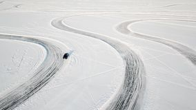 One car driving through the winter forest on country road. Top view from drone. Aerial view of snow covered road in Stock Image