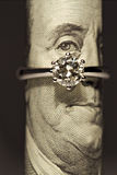 One carat diamond ring. On a one hundred dollar bill royalty free stock photo