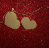 One carton heart attached to the rope on red shining background Stock Image