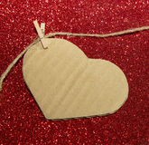 One carton heart attached to the rope on red shining background Royalty Free Stock Photo