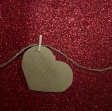 One carton heart attached to the rope on red shining background Stock Images