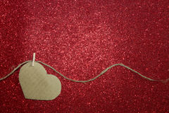 One carton heart attached to rope on red shining background Royalty Free Stock Photos