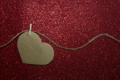 One carton heart attached to the rope on shining background Stock Image