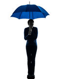 Anxious woman holding umbrella silhouette Royalty Free Stock Photos