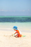 One caucasian boy playing with sand at tropical beach Royalty Free Stock Images