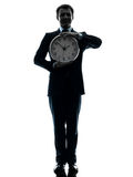 Business man holding clock silhouette Royalty Free Stock Photography