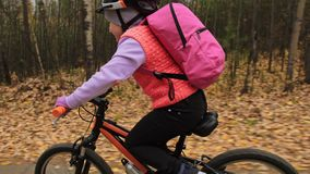 One caucasian children rides bike road in autumn park. Little girl riding black orange cycle in forest. Kid goes do. Bicycle sports. Biker motion ride with stock video footage