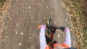 One caucasian children rides bike road in autumn park. Little girl riding black orange cycle in forest. Kid goes do. Pov view. One caucasian children rides bike stock footage