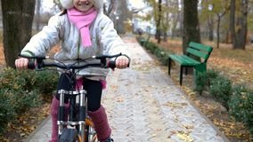 One caucasian children rides bike road in autumn park. Little girl riding black orange cycle in park.. One caucasian children rides bike road in autumn park stock footage