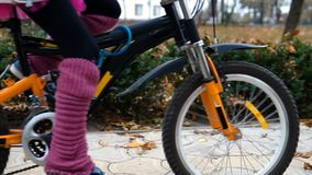 One caucasian children rides bike road in autumn park. Little girl riding black orange cycle in park. Kid goes do bicycle sports stock footage