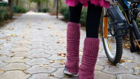 One caucasian children rides bike road in autumn park. Little girl riding black orange cycle in park. Kid goes do bicycle sports stock video footage