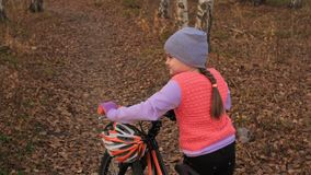 One caucasian children walk with bike in autumn park. Little girl walking black orange cycle in forest. Kid goes do. Bicycle sports. Biker motion ride with stock video footage