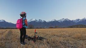 One caucasian children walk with bike in wheat field. Girl walking black orange cycle on background of beautiful snowy. Mountains. Biker motion ride with stock video footage