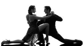 Couple man woman ballroom dancers tangoing  silhouette. One caucasian couple men women ballroom dancers tangoing  in silhouette studio  on white background Royalty Free Stock Photo