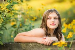 Caucasian High School Senior Girl Outside. One Caucasian High School Senior Girl Looking Back Over Bench Outside By Yellow Flowers Stock Images