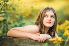 Caucasian High School Senior Girl Outside. One Caucasian High School Senior Girl Looking Back Over Bench Outside By Yellow Flowers Royalty Free Stock Image