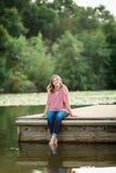 Caucasian High School Senior Girl Outside. One Caucasian High School Senior Girl Sitting on Dock at Lake Outside Summertime Stock Image