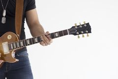 One caucasian man electric guitarist player playing in studio silhouette isolated on white background. Man playing electric guitar standing on white wall stock photo