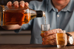 One caucasian man hands close up pouring alcohol in a glass Royalty Free Stock Photography