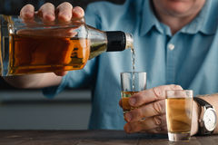 One caucasian man hands close up pouring alcohol in a glass Stock Photo