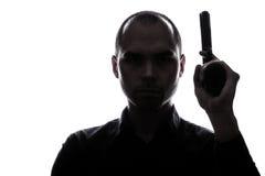 One caucasian  man holding gun portrait silhouette Stock Photo