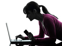 Woman holding credit card computing laptop computer silhouette Royalty Free Stock Images