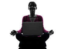 Woman sitting in lotus posture computing laptop computer silhoue Royalty Free Stock Photos