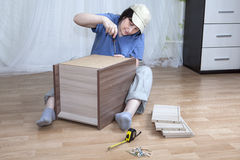 One Caucasian woman self assembly new furniture sitting on floor Stock Images