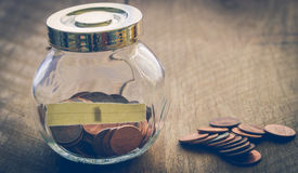 One cent coins on wooden table and in glass jar vintage color st. One cent coins on wooden table and in glass jar - vintage color style effect Stock Image