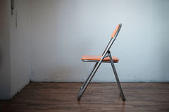 One chair empty in a room meaning solitude Royalty Free Stock Photo