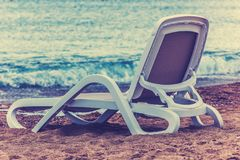 One chaise longue on the beach near the blue sea, close-up royalty free stock images