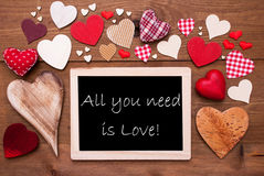 One Chalkbord, Many Red Hearts, All You Need Is Love. Chalkboard With English Text All You Need Is Love. Many Red Textile Hearts. Wooden Background With Vintage Stock Image