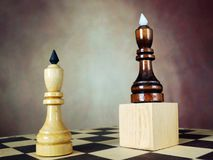One chess king has an advantage over another because he stands on a wooden stand. Superiority. Concept with chess pieces. One chess king has an advantage over Stock Photos