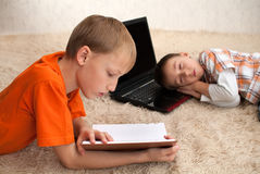 One child read while the other sleeps Royalty Free Stock Images